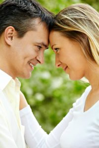 Portrait of young couple looking at each other outdoors